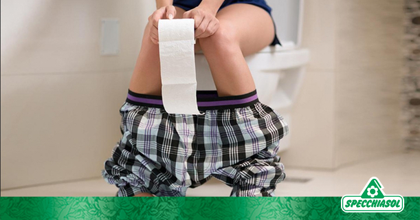 Μία γυναίκα στην τουαλέτα κρατάει το χαρτί καθώς υποφέρει από δυσκοιλιότητα